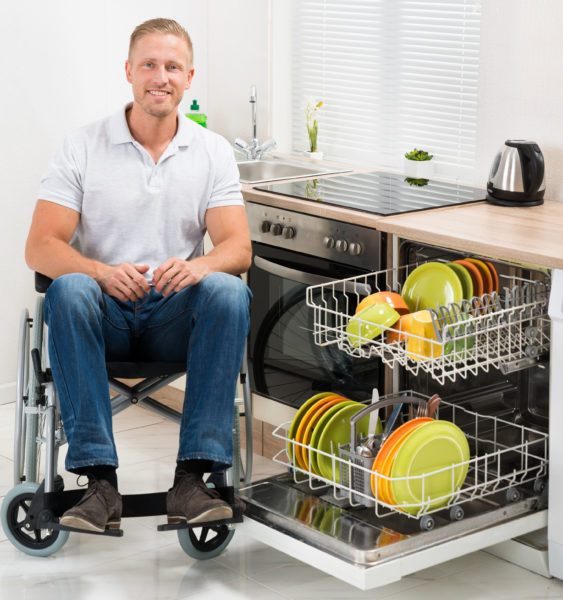 man sitting in a wheelchair while loading the dishwasher