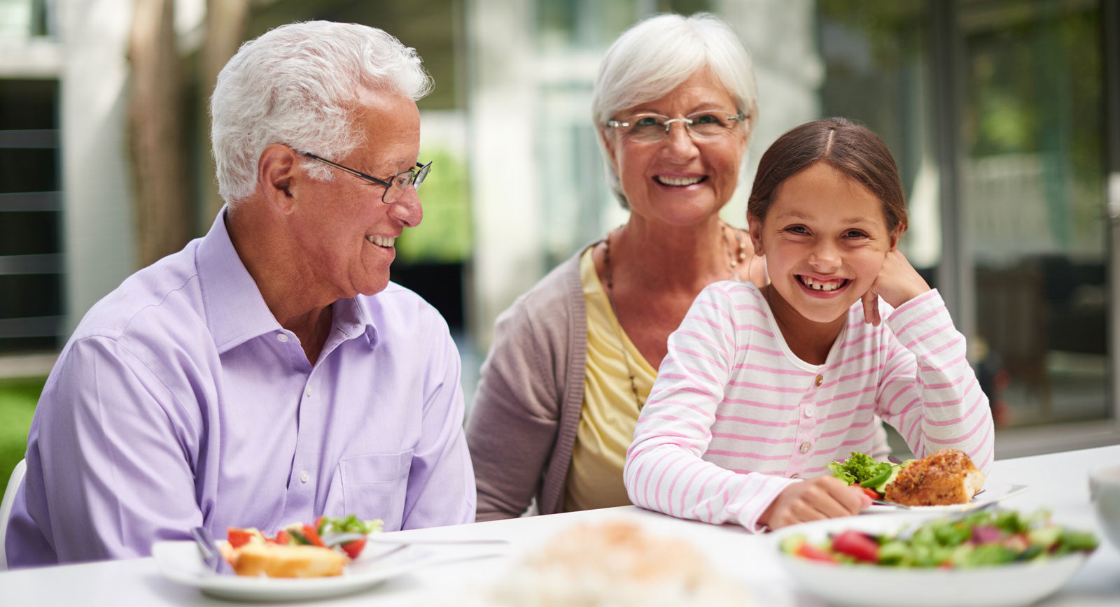 Grandparents eating with grand daughter